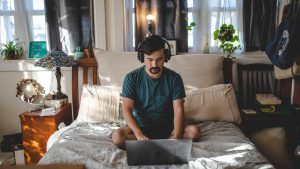 A man wearing headphones and using his laptop on his bed