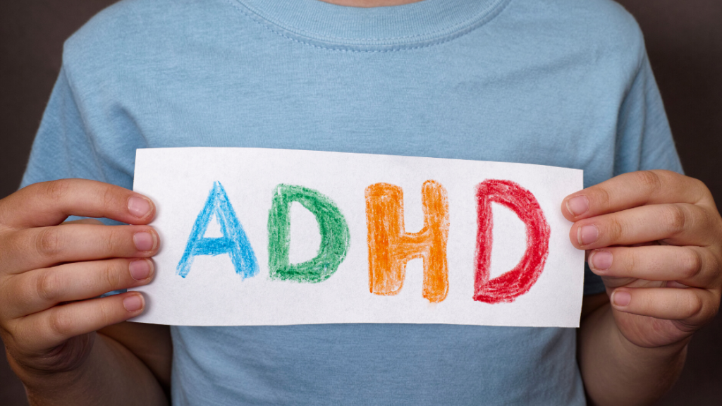 A child holding a paper with ADHD written across it
