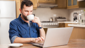 A man sipping on a cup of coffee while working from home