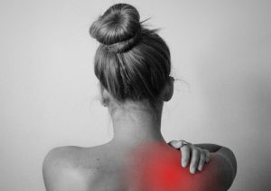 A woman holding the back of her right shoulder